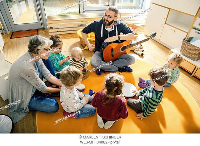 Children and teachers singing and making music in kindergarten