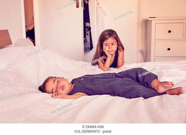 Female toddler, sleeping on bed, older sister watching her sleep