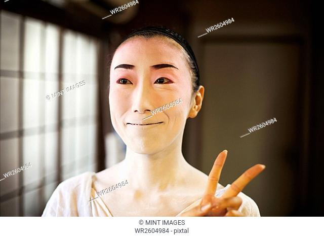 Geisha woman with traditional white face makeup and heavy eyeliner holding up two fingers in a modern gesture