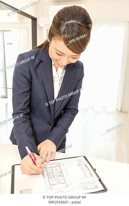 Real Estate Agent Taking Note on Floor Plan