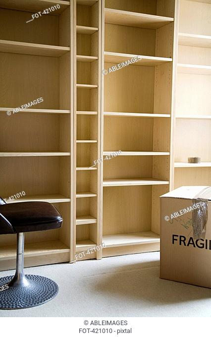 A chair and a cardboard box in front of empty bookshelves