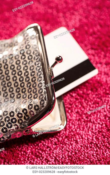 Silver purse and credit card on red carpet