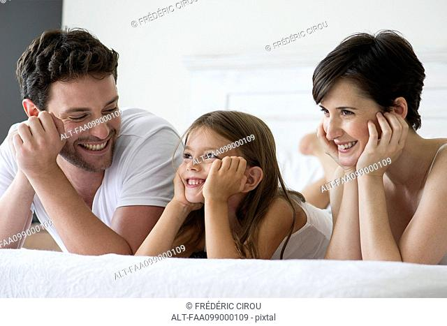 Parents and daughter lying on bed together, portrait