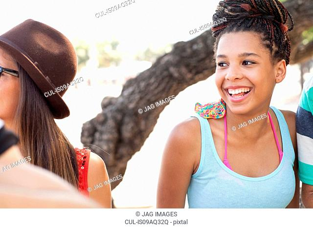 Cropped shot of adult friends chatting and laughing on sidewalk, Copacabana, Rio De Janeiro, Brazil