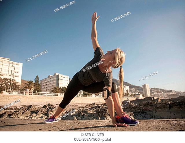 Young woman warming up and stretching at coast, Seapoint, Cape Town, South Africa