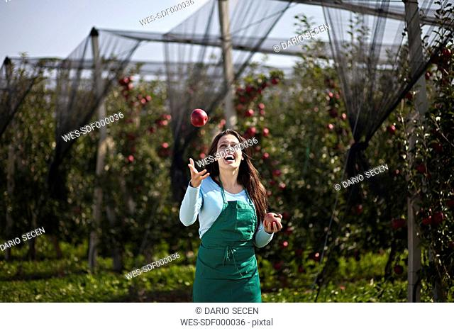Croatia, Baranja, Young woman juggling with apples in apple orchard