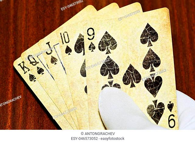 Straight flush poker combination in male hand in glove