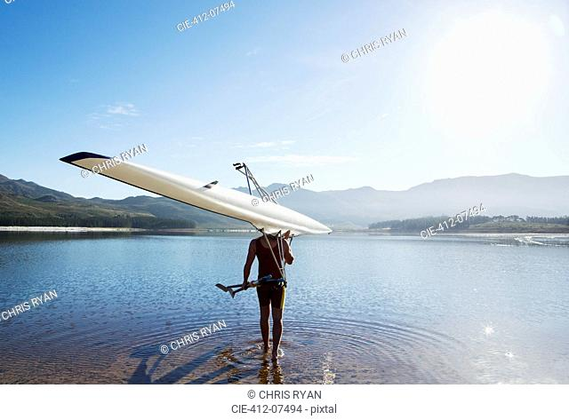 Man carrying rowing scull into lake