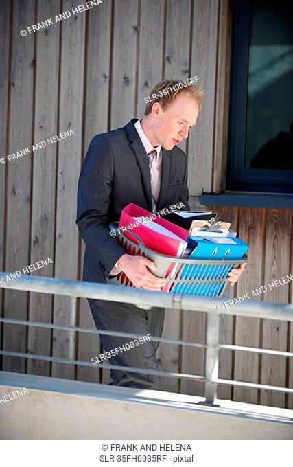 Businessman carrying box of supplies
