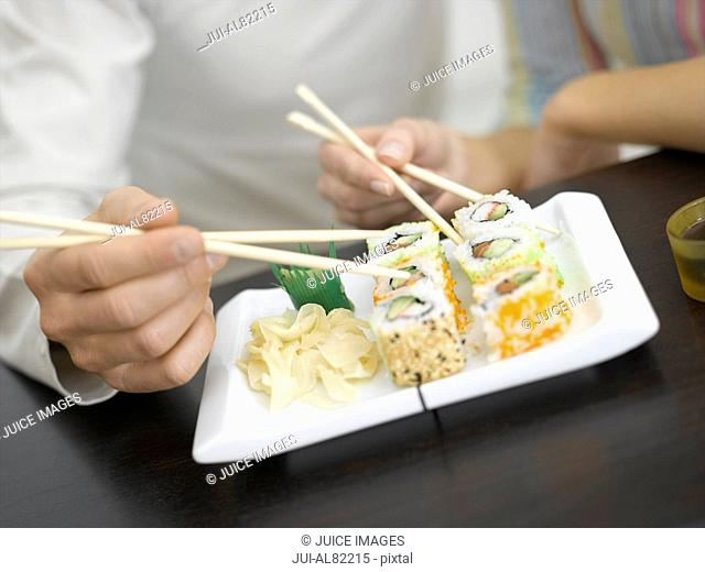 Close up of couple using chopsticks on sushi