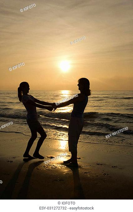 Caucasian mid-adult mother and teenage daughter holding hands spinngin on beach at sunset