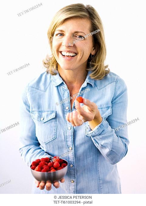 Woman holding bowl of raspberries