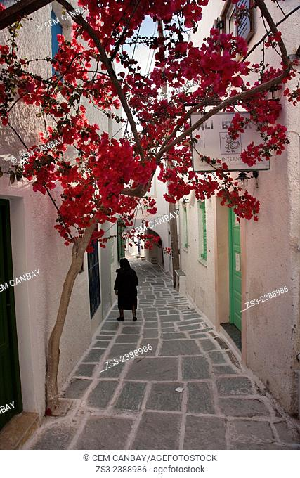 Local woman in black dress walking through the alleys of the town center Chora, Ios, Cyclades Islands, Greek Islands, Greece, Europe