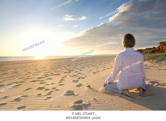 Portugal, Algarve, woman doing yoga exercises at beach house at sunset