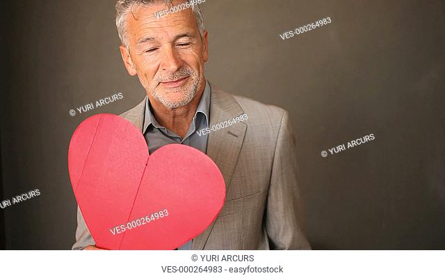 An attractive senior man presenting a red heart to you isolated on a dark background