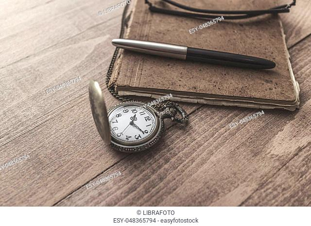 Vintage pocket watch with pen and paper, close up