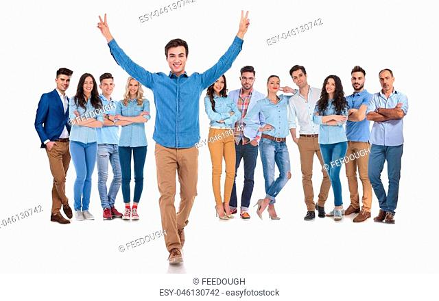 young team leader celebrating success of casual group while walking forward with hands in the air, making peace sign