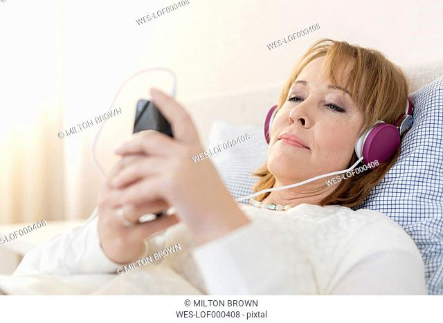 Portrait of woman lying on bed with smartphone and headphones listening music