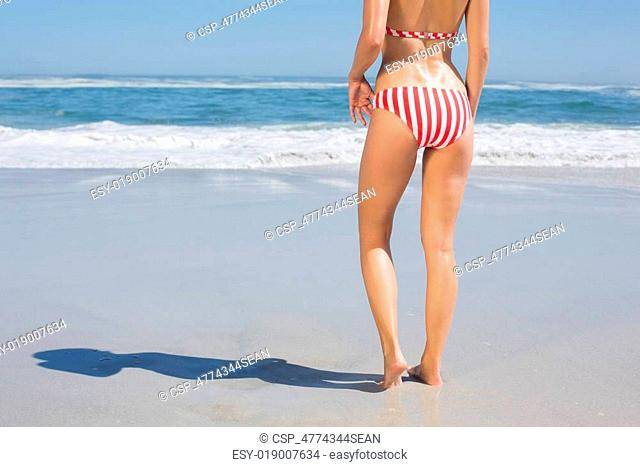 Mid section rear view of fit woman in striped bikini at beach