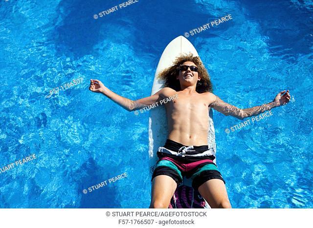 Teenage boy chilling on his surfboard