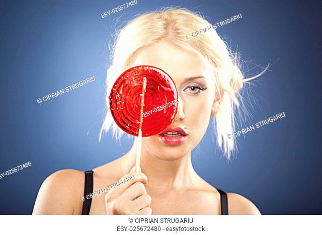Beautiful blonde model hides her face behind a big round red lollipop