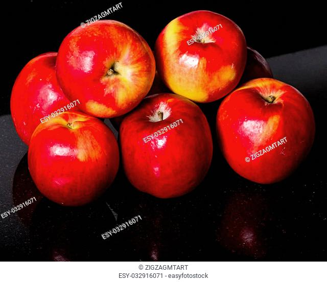 Group of red apples on a black granite kitchen counter