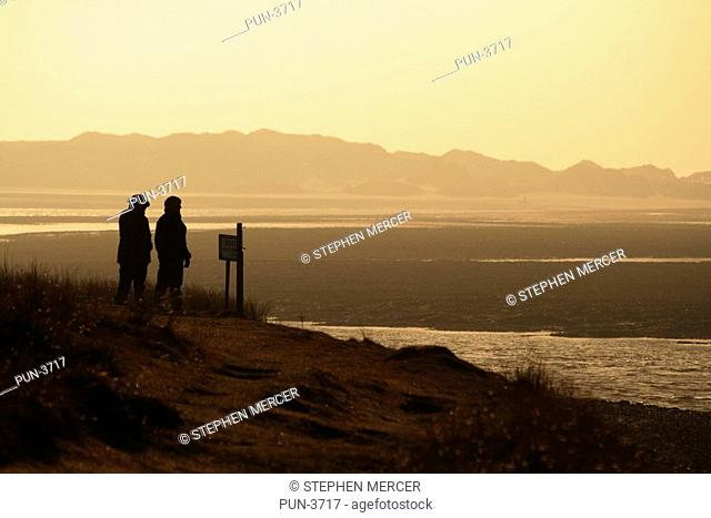 A pair of walkers read a sign on the moorland next to the Ythan estuary, Newburgh