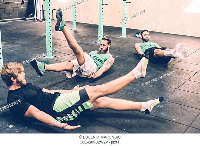 Three male cross trainers doing warm ups in gym