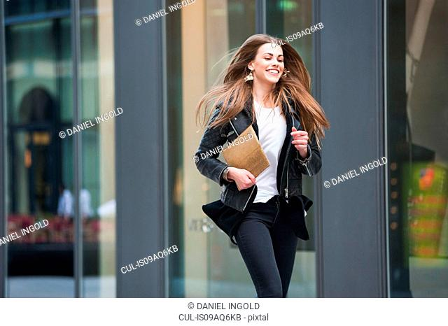 Young woman carrying digital tablet running on street