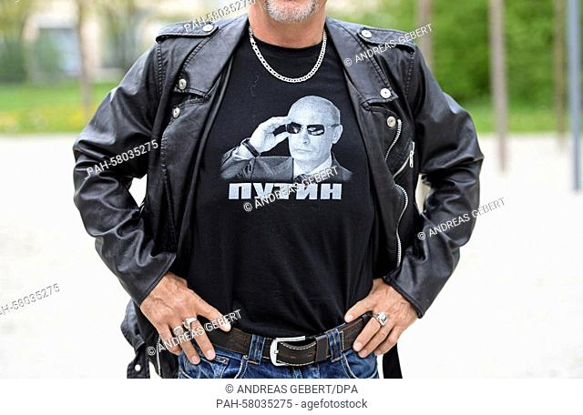A supporter of the Russian bikers' club 'Night Wolves' wears a t-shirt showing a portrait of Russian President Putin underneath his leather jacket as he stands...