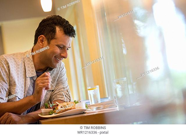 A man eating a snack in a cafe