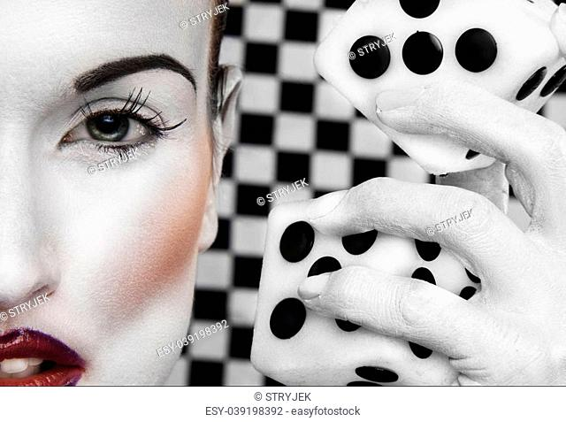 Abstract of a closeup of a portion of a woman's face in white makeup, her white painted hand beside her head holding a large set of dice