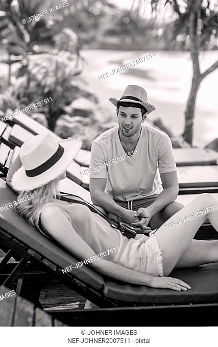 Smiling young couple on lounge chairs