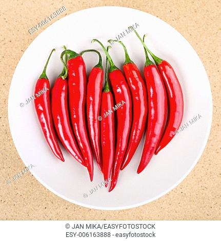 Plate with fresh raw red hot chili peppers on the table