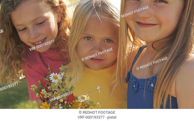 Portrait of three children with bunch of wild flowers in park
