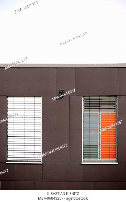 Facade of a modern residential building with metal windows and metal Venetian blind