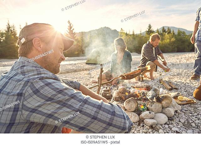 Side view of mature adult man sitting next to campfire, looking away