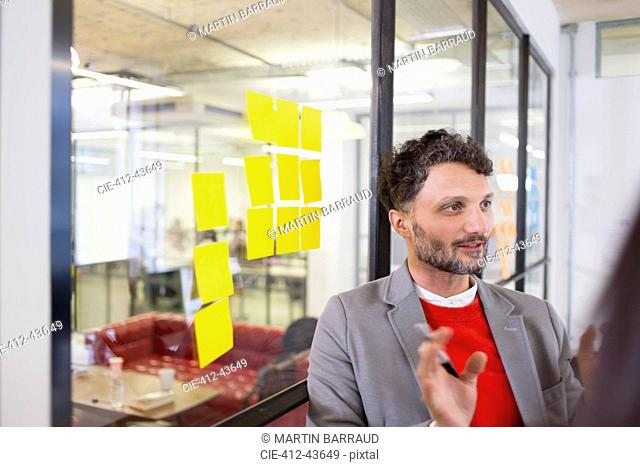 Creative businessman brainstorming with adhesive notes in office