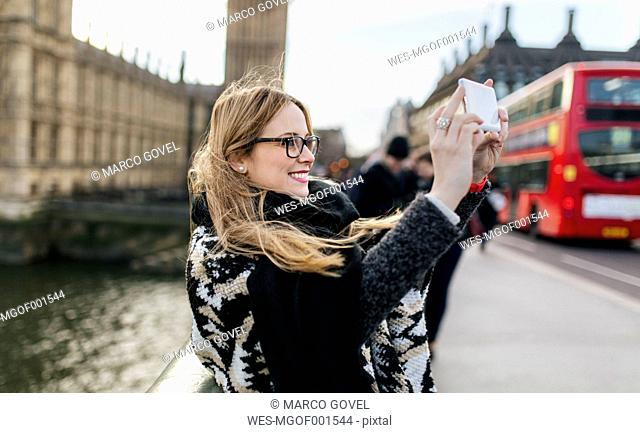UK, London, young woman taking a selfie on Westminster Bridge