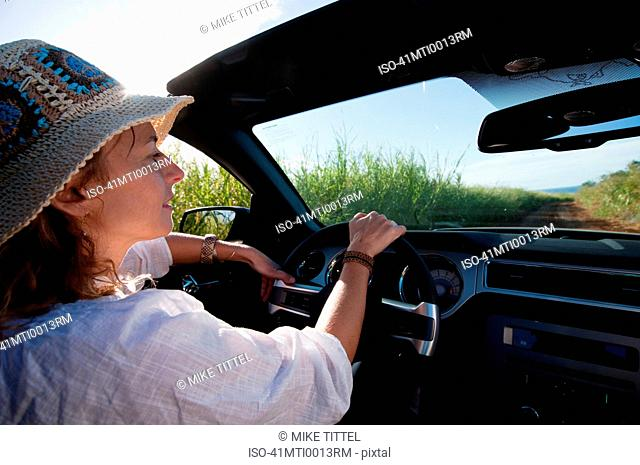 Woman driving convertible on dirt road