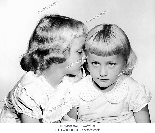 Little girl whispering into sisters ear