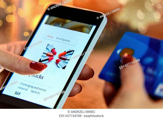 Modern Woman makes shopping via smartphone and a credit card in the e-store