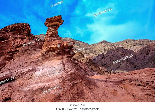Outcrops of red sandstone unusual forms. Dry mountains of Eilat on a warm day in January