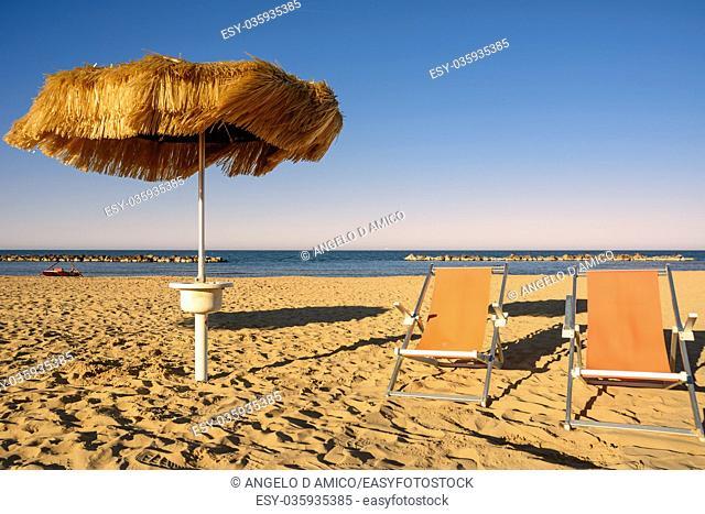 Palm umbrellas on the beach and pier in background in Francavilla al Mare