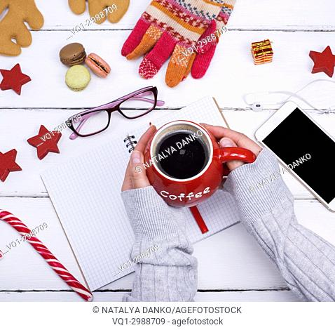 ceramic red mug with black coffee in female hands over a table with an empty open notebook, kind of scrap