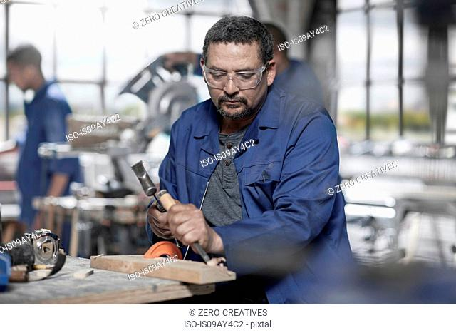 Carpenter using chisel on wood in workshop