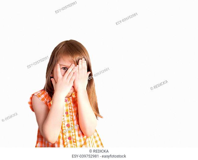 a little girl peeking through the palm