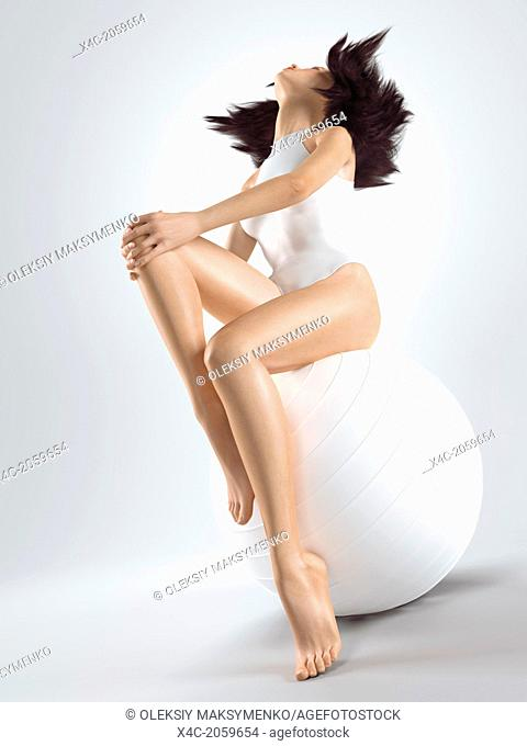 Young woman with fit slim body sitting on white exercise ball isolated on white background. Fitness and health concept. Photorealistic 3D illustration
