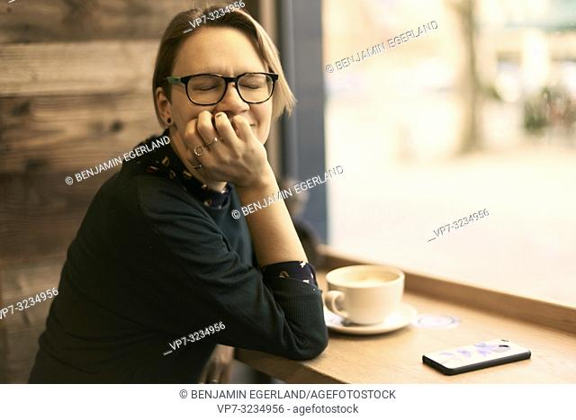 woman sitting at table with coffee cup indoors in café next to window, taking break, squinny eyes, in Munich, Germany