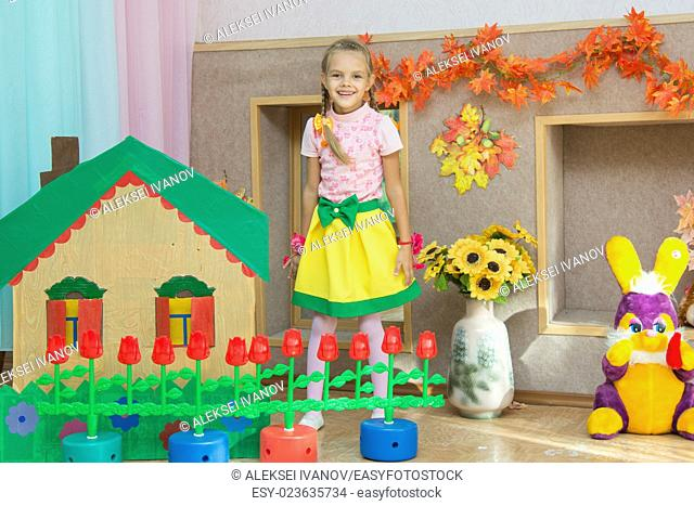 Six year old girl stands in the scenery of a country house and a flower bed at the matinee in kindergarten